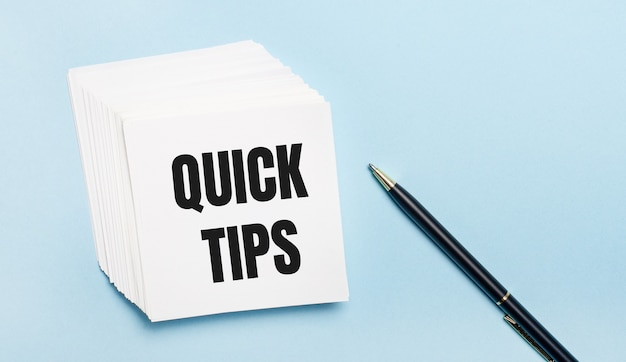 Op een lichtblauwe achtergrond staat een zwarte pen en een stapel wit notitiepapier met de tekst quick tips