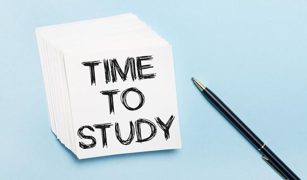 Op een lichtblauwe achtergrond staat een zwarte pen en een stapel wit notitiepapier met de tekst time to study
