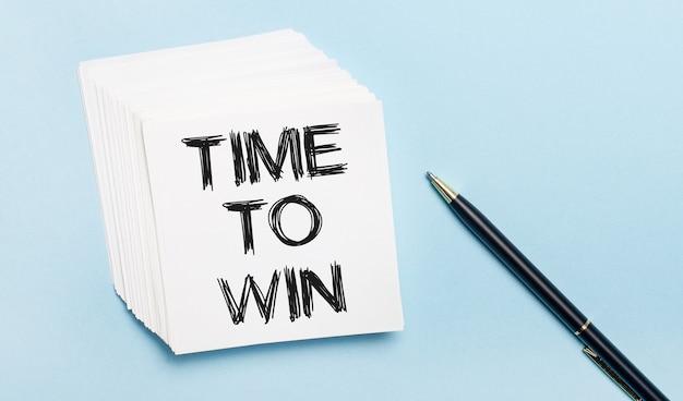 Op een lichtblauwe achtergrond staat een zwarte pen en een stapel wit notitiepapier met de tekst time to win