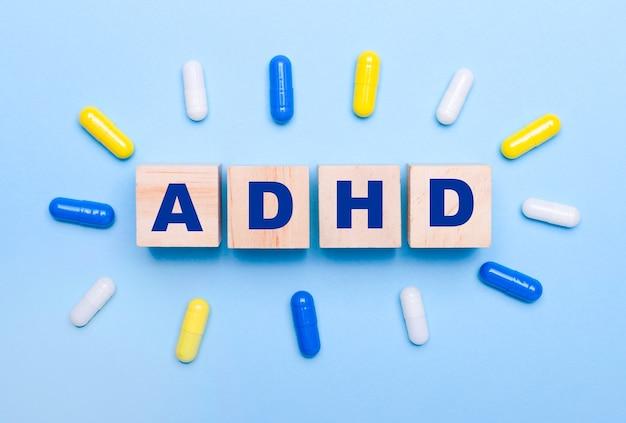 Op een lichtblauwe achtergrond, veelkleurige pillen en houten blokjes met de tekst adhd. medisch concept