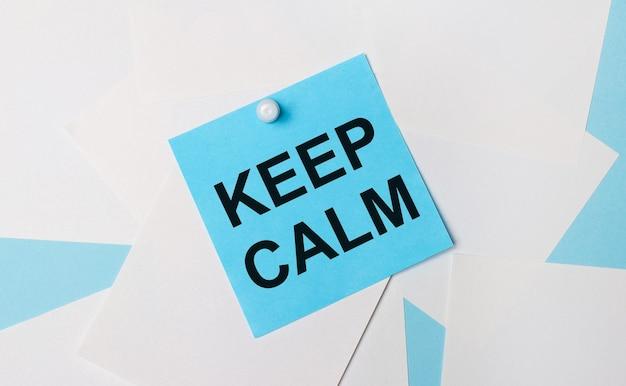 Op een lichtblauwe achtergrond, witte vierkante vellen papier. met een witte paperclip is er een lichtblauwe vierkante sticker met de tekst keer calm op bevestigd.