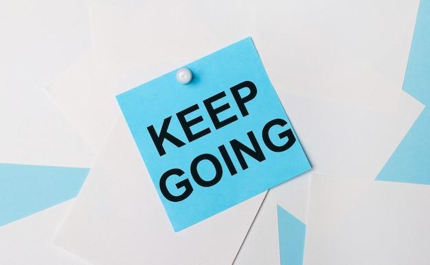 Op een lichtblauwe achtergrond, witte vierkante vellen papier. met een witte paperclip is er een lichtblauwe vierkante sticker met de tekst keer going op bevestigd.