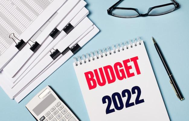 Op een lichtblauwe achtergrond zijn er documenten, een bril, een rekenmachine, een pen en een notitieboekje met de tekst budget 2022. close-up van de werkplek. bedrijfsconcept