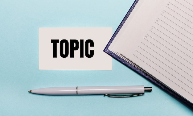 Op een lichtblauwe ondergrond een open notitieboekje, een witte pen en een kaartje met de tekst topic