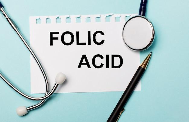 Op een lichtblauwe ondergrond een stethoscoop, een pen en een vel papier met de inscriptie folic acid