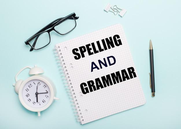 Op een lichtblauwe tafel liggen zwarte glazen en een pen, een witte wekker, witte paperclips en een notitieboekje met de woorden spelling and grammar. bedrijfsconcept