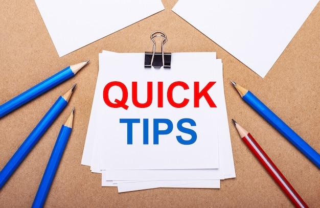Op een lichtbruine ondergrond, blauwe en rode potloden en wit papier met de tekst quick tips