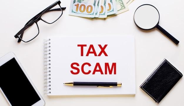 Op een lichte achtergrond, dollars, glazen, een vergrootglas, een telefoon, een pen en een notitieboekje met het opschrift tax scam