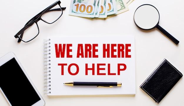 Op een lichte achtergrond, dollars, glazen, een vergrootglas, een telefoon, een pen en een notitieboekje met het opschrift we zijn hier om te helpen. bedrijfsconcept