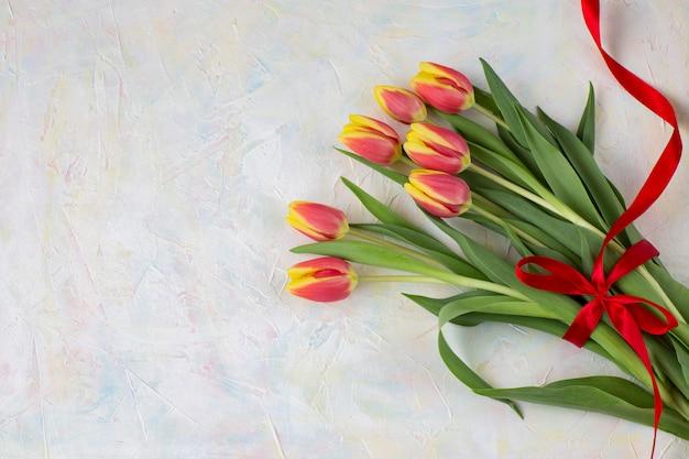 Op een lichte achtergrond een boeket van tulpen en een rood lint