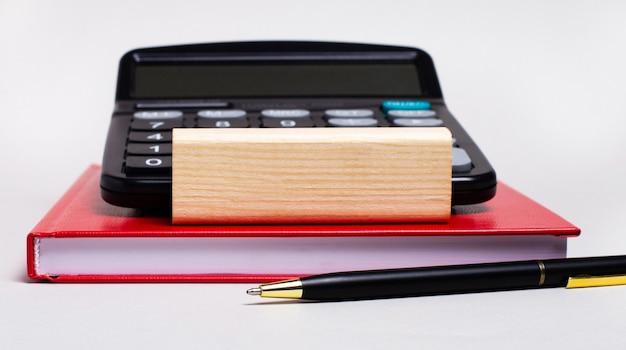 Op een lichte achtergrond, een bordeauxrood notitieboekje, een rekenmachine, een pen en een houten blok met een plek om tekst in te voegen.