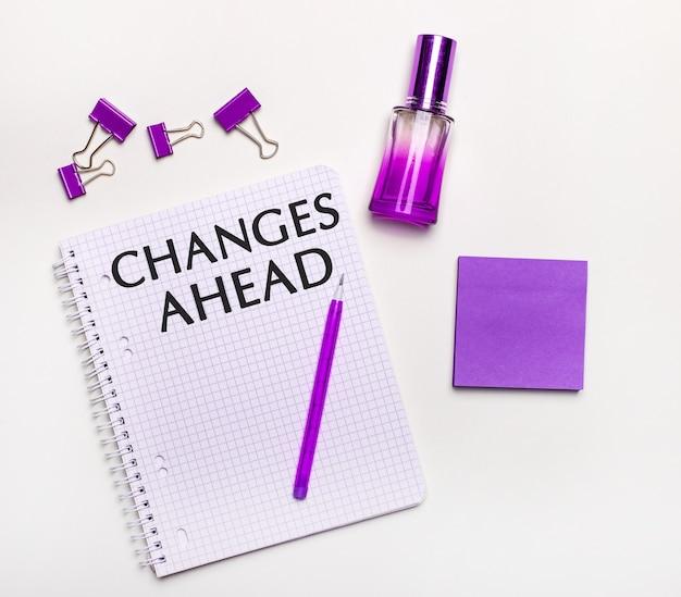 Op een lichte achtergrond - een lila geschenk, parfum, lila zakelijke accessoires en een notitieboekje met een lila inscriptie changes ahead
