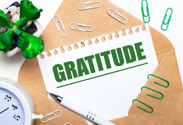 Op een lichte achtergrond een open envelop, een witte wekker, een groene plant, witte en groene paperclips, een witte pen en een vel papier met de tekst dankbaarheid