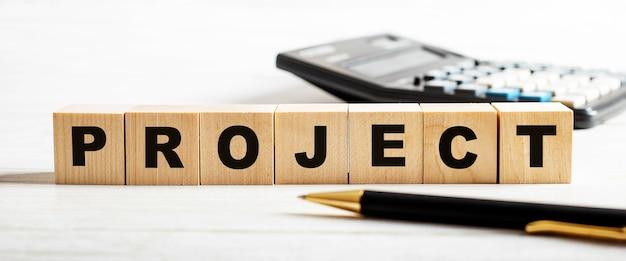 Op een lichte achtergrond, een pen, rekenmachine en houten blokjes met het opschrift project. onscherp