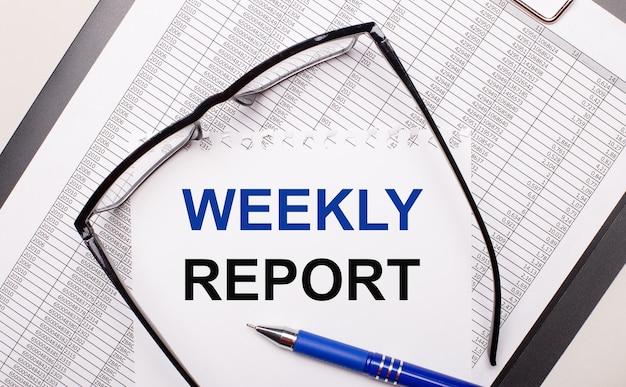 Op een lichte achtergrond een rapport, een bril met zwart montuur, een pen en een vel papier met de tekst wekelijks verslag. bedrijfsconcept