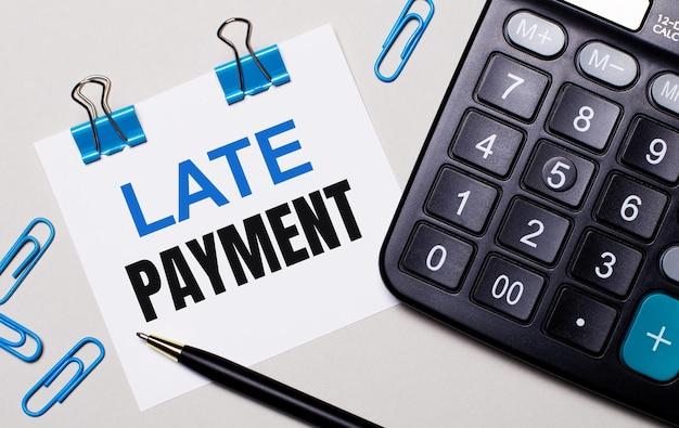 Op een lichte achtergrond een rekenmachine, een pen, blauwe paperclips en een vel papier met de tekst late payment. uitzicht van boven