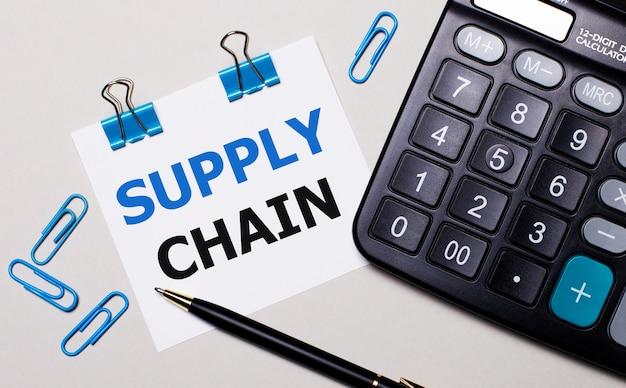 Op een lichte achtergrond een rekenmachine, een pen, blauwe paperclips en een vel papier met de tekst supply chain. uitzicht van boven