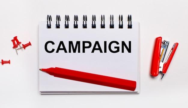 Op een lichte achtergrond, een rode pen, een rode nietmachine, rode paperclips en een notitieboekje met het opschrift campaign