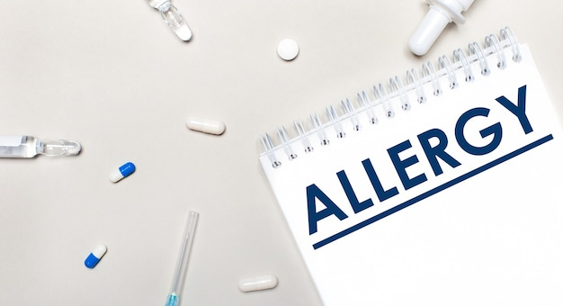 Op een lichte achtergrond, een spuit, een stethoscoop, flesjes met medicijnen, een ampul en een wit notitieblok met de tekst allergy. medisch concept