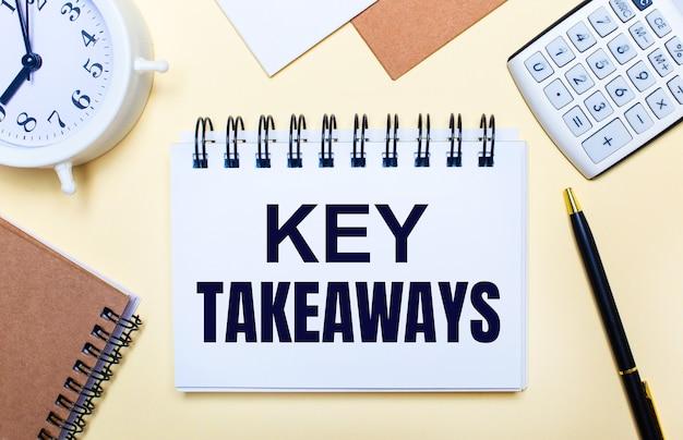 Op een lichte achtergrond een witte wekker, een rekenmachine, een pen en een notitieboekje met de tekst key takeaways. plat leggen
