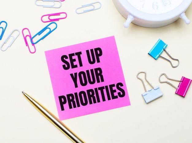 Op een lichte achtergrond een witte wekker, roze, blauwe en witte paperclips, een gouden pen en een roze sticker met de tekst set up your priorities