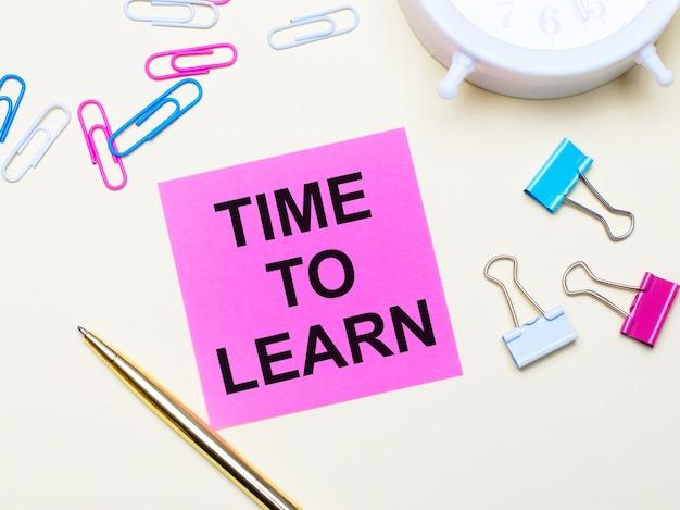 Op een lichte achtergrond een witte wekker, roze, blauwe en witte paperclips, een gouden pen en een roze sticker met de tekst time to learn