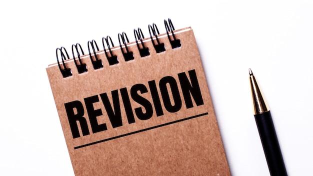 Op een lichte achtergrond, een zwarte pen en een bruin notitieboekje op zwarte veren met het opschrift revision