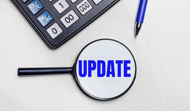 Op een lichte achtergrond, een zwarte rekenmachine, een blauwe pen en een vergrootglas met tekst in het woord update. uitzicht van boven