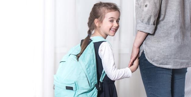 Op een lichte achtergrond gaan ouder en basisschoolleerling hand in hand. terug naar school-concept