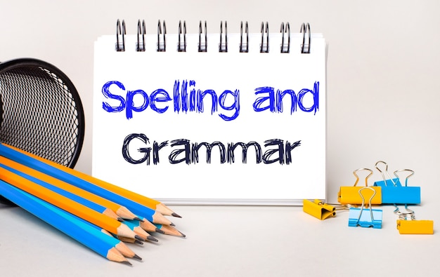Op een lichte achtergrond, gele en blauwe potloden en paperclips en een wit notitieboekje met de tekst spelling and grammar
