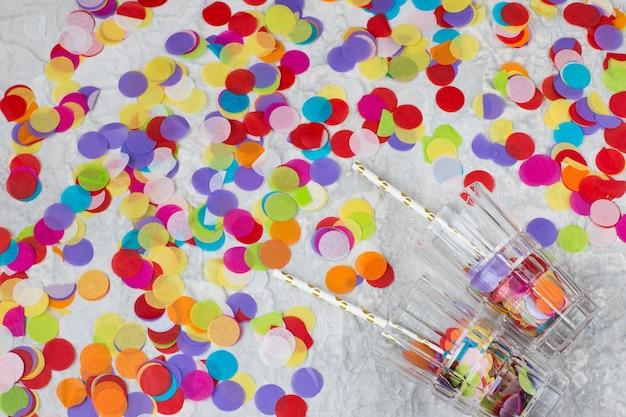 Op een lichte achtergrond heldere confetti en cocktailglazen