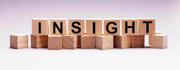 Op een lichte achtergrond, houten kubussen met de tekst insight