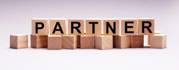 Op een lichte achtergrond, houten kubussen met de tekst partner