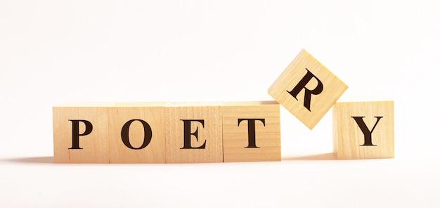 Op een lichte achtergrond, houten kubussen met de tekst poetry