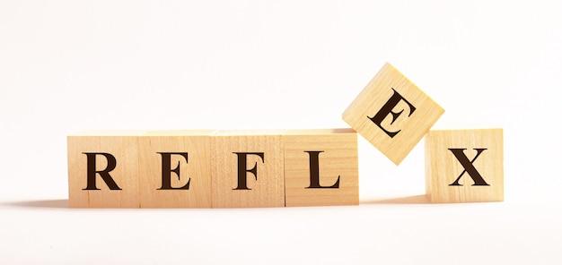 Op een lichte achtergrond, houten kubussen met de tekst reflex
