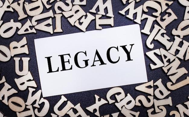 Op een lichte achtergrond, houten letters van het engelse alfabet en een witte kaart erin met het woord legacy