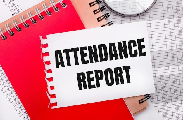 Op een lichte achtergrond - rapporten, een vergrootglas, bruine en rode blocnotes en een witte blocnote met de tekst attendance report. bedrijfsconcept