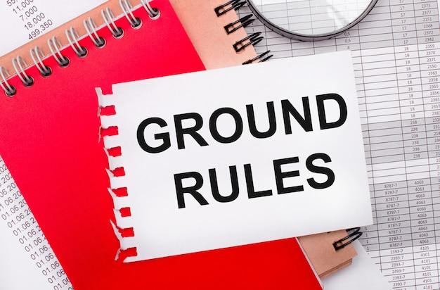 Op een lichte achtergrond - rapporten, een vergrootglas, bruine en rode blocnotes, en een witte blocnote met de tekst ground rules. bedrijfsconcept