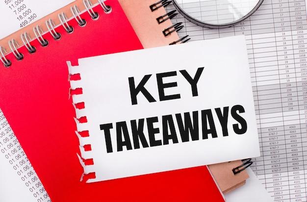 Op een lichte achtergrond - rapporten, een vergrootglas, bruine en rode blocnotes, en een witte blocnote met de tekst key takeaways. bedrijfsconcept