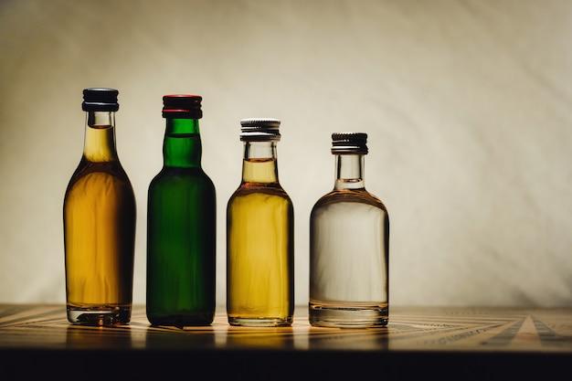 Op een lichte achtergrond staan verschillende alcoholflessen op tafel.