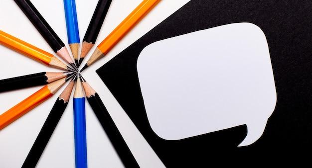Op een lichte achtergrond, veelkleurige potloden en op een zwarte achtergrond, een witte blanco kaart met een plek om tekst in te voegen.