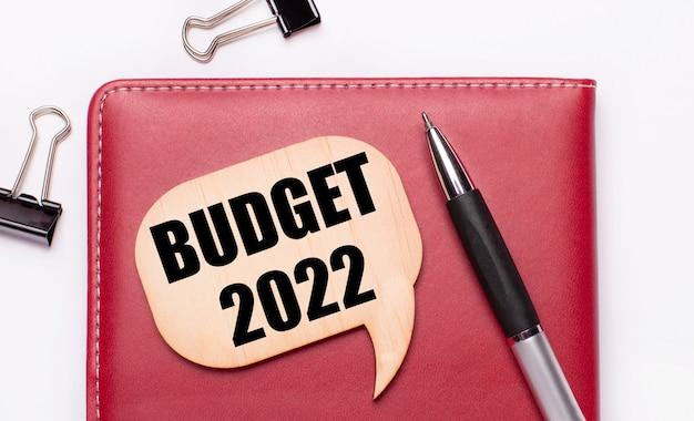 Op een lichte achtergrond zijn er zwarte paperclips, een pen, een bordeauxrode notitieblok een houten bord met de tekst budget 2022