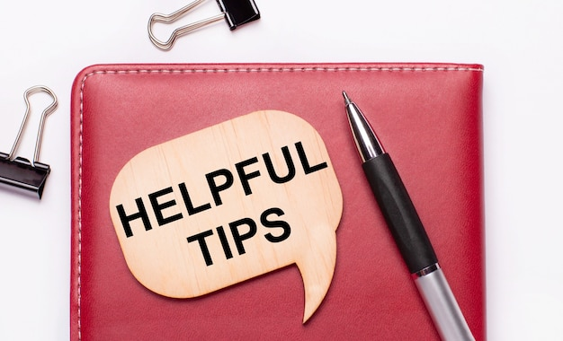 Op een lichte achtergrond zijn er zwarte paperclips, een pen, een bordeauxrode notitieblok een houten bord met de tekst nuttige tips
