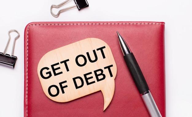 Op een lichte achtergrond zijn er zwarte paperclips, een pen, een bordeauxrood notitieblok een houten bord met de tekst get out of debt