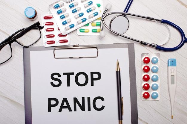 Op een lichte houten achtergrond is er papier met het opschrift stop panic, een stethoscoop, kleurrijke pillen, glazen en een pen