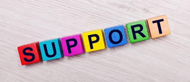 Op een lichte houten achtergrond op veelkleurige heldere houten kubussen het woord support