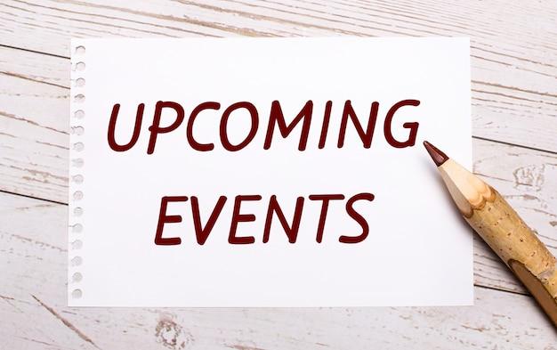 Op een lichte houten ondergrond een kleurpotlood en een wit vel papier met de tekst upcoming events