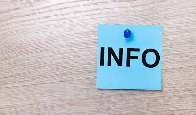 Op een lichte houten ondergrond - een lichtblauwe vierkante sticker met de tekst info