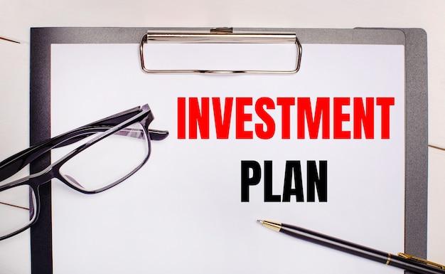 Op een lichte houten ondergrond glazen, een pen en een vel papier met de tekst investment plan. bedrijfsconcept