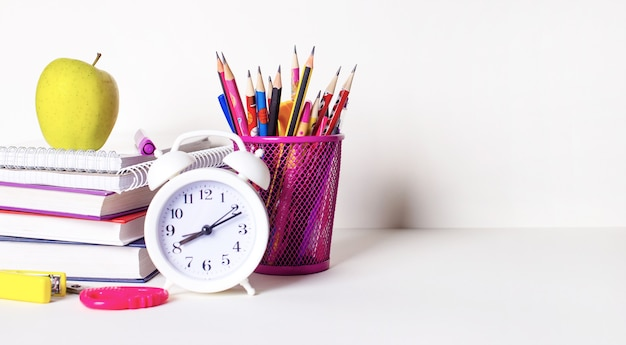 Op een lichte ondergrond boeken, briefpapier, potloden en pennen in een glas, een appel en een witte wekker. school concept